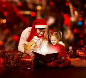 Christmas family reading book. Father and child opening magic fa. Iry tale over red background stock images