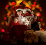 Christmas Family Kids Open Bag, Xmas Presents Gift Toys. Christmas Family, Kids and Parents Open Light Bag with Presents Gift Toys over defocused Xmas Tree royalty free stock images