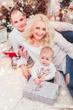 Christmas family smiling near the Xmas tree. Living room decorated by Christmas tree and present gift box royalty free stock photography