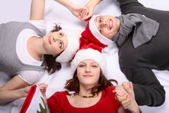 Christmas in family with teen girl. Teenager girl holding mother and father's hands in a circle with Christmas hats Stock Image