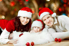 Christmas family of three persons in red hats royalty free stock photography