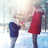 Christmas, family and winter concept - child son gives mother gift box in sunny winter Stock Photo