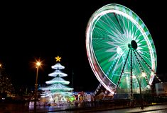Christmas fancy fair wheel. Night view on a Christmas fancy fair with a lighted wheel and turning Christmas tree and star light, in Leuven, Belgium Stock Photography