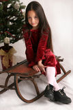 Christmas fashion. Little girl in dress sitting on old-fashioned sled in front of Christmas tree Stock Photo