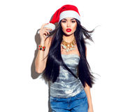 Christmas fashion model girl with long straight flying hair in red santa hat Royalty Free Stock Image