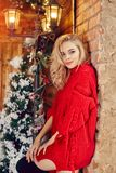 Christmas Fashion woman blonde in the red sweater, having fun and posing against the Christmas tree and lamppost. Winter. And Christmas tree in village house stock images