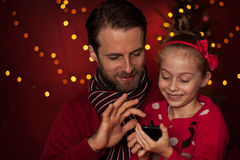 Christmas - father and daughter playing game on mobile phone. Christmas - smiling father and daughter playing game on mobile phone. Happy family time, dark red royalty free stock images