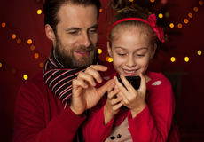 Christmas - father and daughter playing game on mobile phone. Christmas - smiling father and daughter playing game on mobile phone. Happy family time, dark red royalty free stock photo