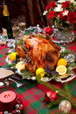 Christmas Feast Turkey. Garnished roast turkey on Christmas-decorated table with candles and flutes of champagne Royalty Free Stock Image