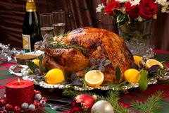Christmas Feast Turkey. Garnished roast turkey on Christmas-decorated table with candles and flutes of champagne Stock Image