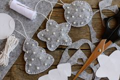 Things to make with felt for Christmas. Gray felt fir tree, ball and star ornaments with white beads. Scissors, thread, needle Royalty Free Stock Photography