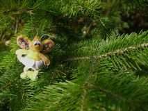 Christmas felt decoration on a spruce branch. Handmade bauble figurines a butterfly. Holiday background with a copy space