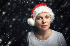 Christmas female beauty portrait with snowflakes. Beautiful adult woman with blue eyes wearing Santa Claus hat and looking at camera, calm friendly positive Royalty Free Stock Photography