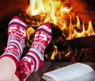 Christmas female legs in socks on the background of a burning fi Stock Image