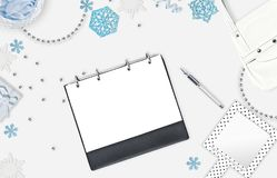 Christmas feminine background with place for text. Blue snowflakes, shiny beads, notebook and pen on white background. Plan for th Royalty Free Stock Photography