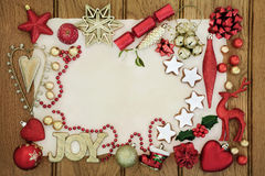 Christmas Festive Background Border. Christmas background border with gold joy sign, gingerbread biscuits, bauble decorations, holly, mistletoe and foil wrapped Royalty Free Stock Photography