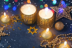 Christmas festive background with candles and golden decorations over dark board Royalty Free Stock Photo