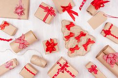 Christmas festive background - different gifts boxes of kraft paper, blank labels and red ribbons, bows on soft white wood board. Christmas festive background royalty free stock image