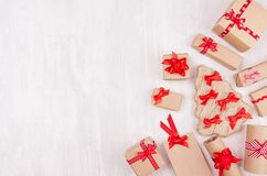 Christmas festive background - different gifts boxes of kraft paper and red ribbons, bows as border on soft white wood board. royalty free stock photography