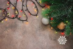 Christmas festive background, fir branch, balls and garland, dark rustic background. Top view, flat lay, copy space.  stock photo