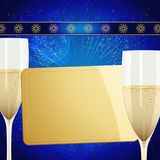 Christmas gift golden card and champagne glasses on blue. Christmas Festive Blue Background with Golden Gift Tag Champagne Glasses and Decorated Ribbon Stock Photos