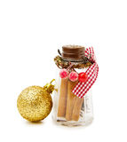 Christmas festive cinnamon jar. Celebrating Christmas holidays with festive cinnamon jar and golden bauble. Isolated on white Stock Images