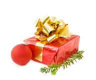 Christmas festive gifts and red bauble. Celebrating Christmas with festive gifts, red bauble and evergreen tree branch. Isolated on white background with room Stock Image