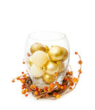 Christmas festive golden baubles in glass bowl. Celebrating Christmas with sparkling golden baubles in a glass bowl. Isolated on white background. This image is Stock Image