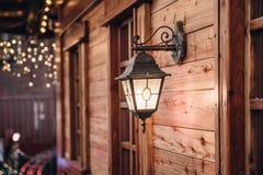 Christmas lantern. Festive illumination on a wooden house. Christmas Festive illumination lantern on a building. Lights background. Festive illumination on a stock photography
