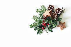 Christmas festive styled composition. Winter floral arrangement. Pine cones, fir tree branches, red holly berries and royalty free stock image