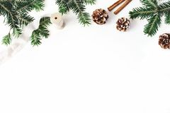 Christmas festive styled stock composition. Fir tree branches border. Pine cones, cinnamon and silk ribbon on white. Wooden background. Flat lay, top view. Copy stock photography
