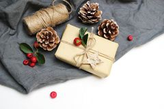 Christmas festive styled stock image composition. Handmade Christmas gift box, red berries, pine cones isolated on grey. Linen blanket. Top view. Winter holiday royalty free stock photo