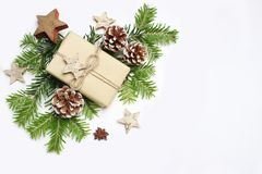 Christmas festive styled stock image composition. Handmade craft paper gift box, pine cones, wooden and anise stars and. Fir tree branches on white wooden royalty free stock photography