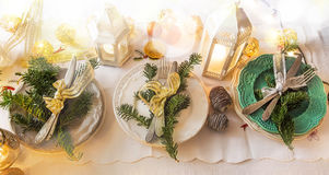 Christmas festive table setting decoration with tableware, ribbon, lantern with candles stock images