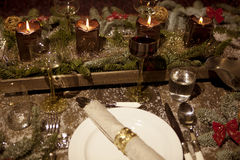 Christmas festively tiled. Christmas place setting with candles, are wine glasses on the table, pine tree branches are adorned with decorative snow Stock Photos