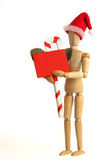 Christmas figure holding sign. Wooden figure with santa hat holding candy cane sign Royalty Free Stock Photo