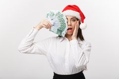 Christmas and finance concept - Young business woman showing money closing her face with surprise expression. Christmas and finance concept - Young business Stock Photos