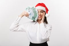 Christmas and finance concept - Young business woman showing money closing her face with surprise expression. Christmas and finance concept - Young business Stock Images