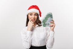 Christmas and Financial concept - Young confident business woman showing money in front of her with happy face. Christmas and Financial concept - Young Royalty Free Stock Photos