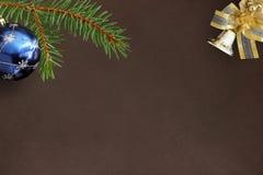 Christmas fir branch, blue balloon and decorative bell on dark b Royalty Free Stock Photos