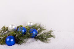Christmas fir branch with blue christmas balls in snow Royalty Free Stock Images
