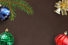 Christmas fir branch, blue, green ribbed and red wavy balloon and decorative bell on dark Royalty Free Stock Photography