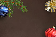 Christmas fir branch, blue and red wavy balloon and decorative bell on dark Stock Image