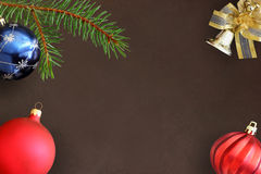 Christmas fir branch, blue and red wavy dull balloon and decorative bell on dark Royalty Free Stock Photo