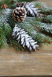 Christmas fir branch covered with artificial snow on boards Royalty Free Stock Images