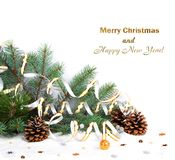 Christmas fir branch with pine cones, gold streamers and stars Royalty Free Stock Photo