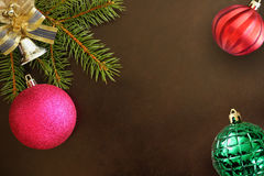 Christmas fir branch, pink, red wavy and green ribbed ball, decorative bell on dark Stock Photos