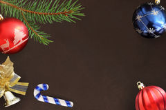 Christmas fir branch, stick, red wavy, and blue balls and decorative bell on dark Stock Photos