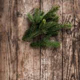Christmas fir branch on wooden holiday background. Xmas and New Year theme. Flat lay, top view stock images