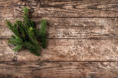 Christmas fir branch on wooden holiday background. Xmas and New Year theme. Flat lay, top view stock photography